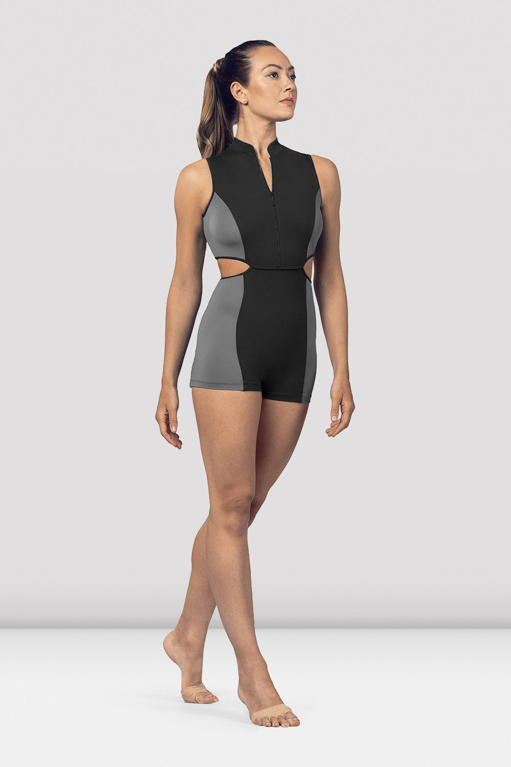 Black Bloch Ladies Zip Front Cut Out Biketard on female model in parallel foruth position facing corner