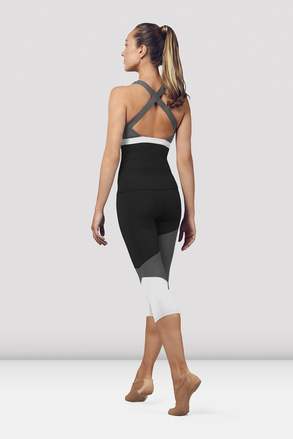 Black Bloch Ladies Scoop Neck Cross Back Tank Top on female model in parallel fourth position on releve facing back corner