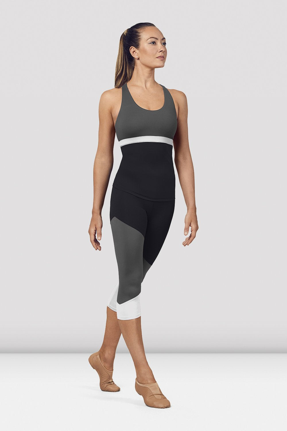Black Bloch Ladies Scoop Neck Cross Back Tank Top on female model in parallel fourth position on releve facing corner