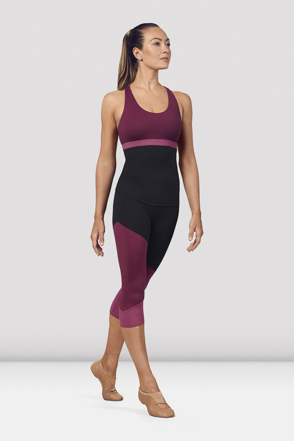 Dewberry Bloch Ladies Scoop Neck Cross Back Tank Top on female model in parallel fourth position on releve facing corner