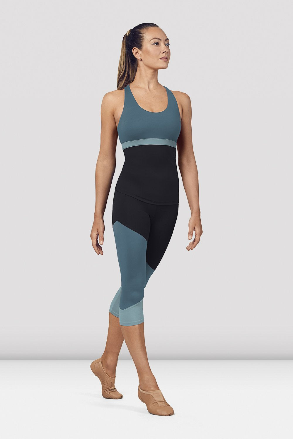 Seaport Bloch Ladies Scoop Neck Cross Back Tank Top on female model in parallel fourth position on releve facing corner