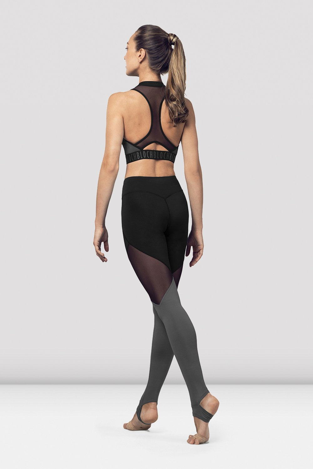 Black Bloch Ladies Zip Front Mesh Back Crop Top on female model in parallel fourth position on releve facing back corner