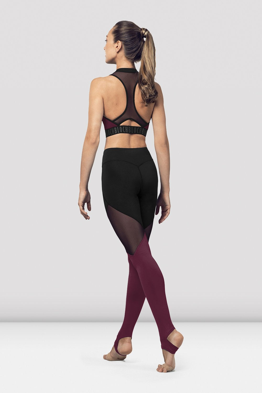 Dewberry Bloch Ladies Full Length Leggings on female model in parallel fourth position on releve facing back corner