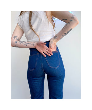Shoulder to knees photo of model wearing sister jeans in classic blue itochu denim facing the back.