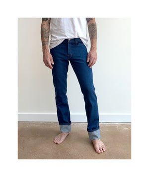 Waist down photo of model wearing mens REVEREND style jeans facing forward.