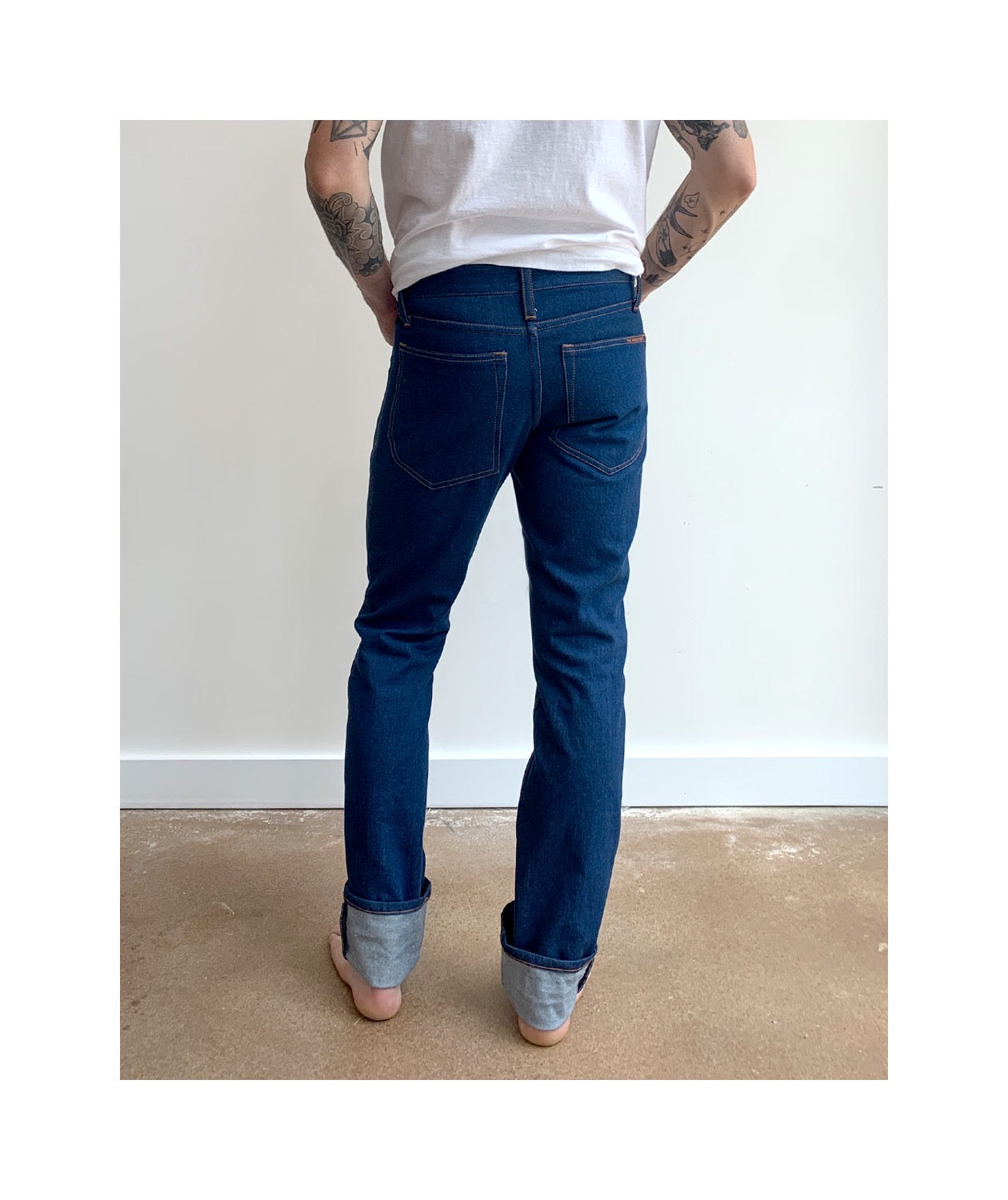 Waist down photo of model wearing mens REVEREND style jeans, not facing the camera to show back of jeans.
