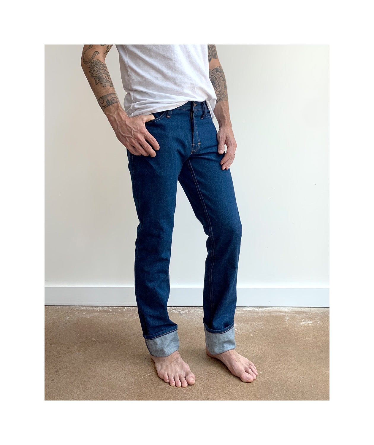 Waist down photo of model wearing mens REVEREND style jeans slightly angled to show side of jeans.