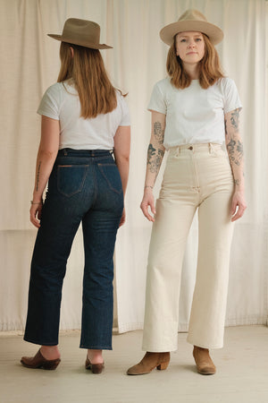 Two models in Stetson felt hats wearing HIGH POPE jeans. One in denim blue and the other in cream. One facing the backdrop and the other facing the camera.