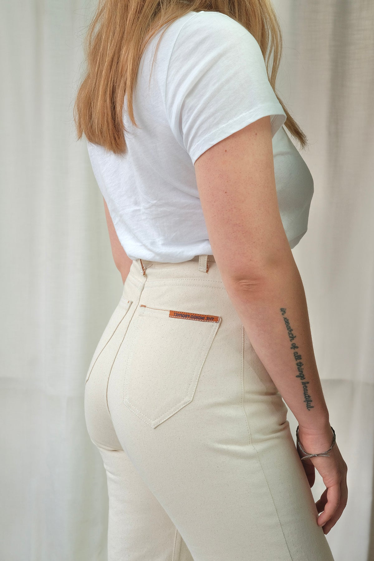 Close up image of model's side from shoulders to knees wearing HIGH POPE in cream with back pocket visable.