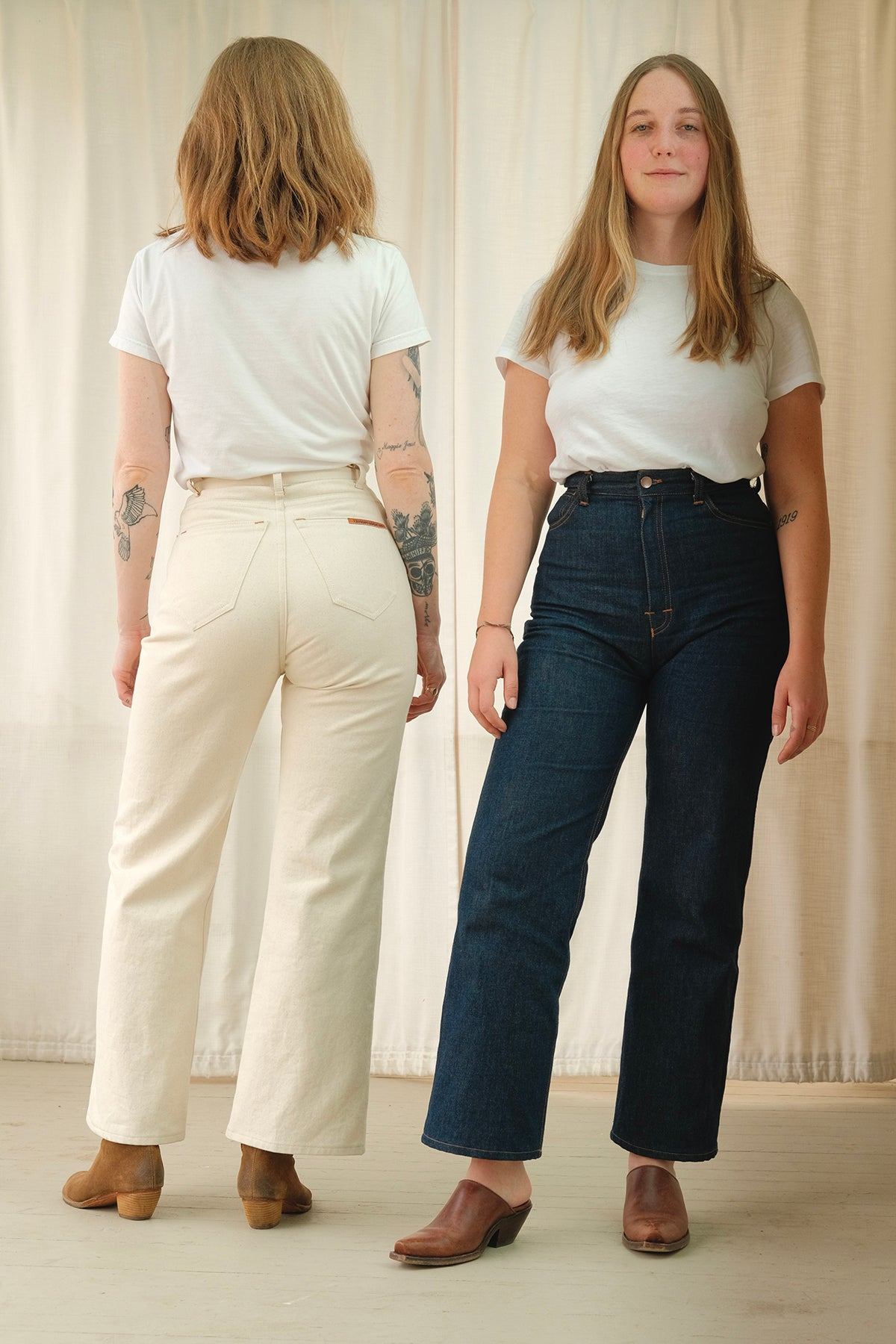 Two models wearing HIGH POPE jeans. One in denim blue and the other in cream. One facing the backdrop and the other facing the camera.