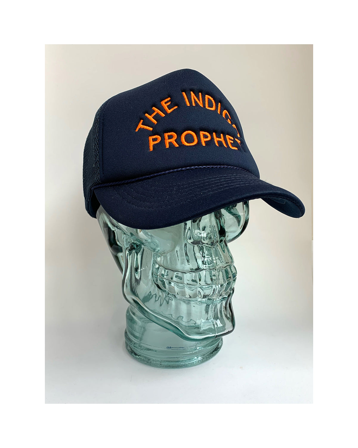 Glass mannequin skull head on white background  wearing a trucker style hat in blue aka indigo with The Indigo Prophet stitched on the front in orange.