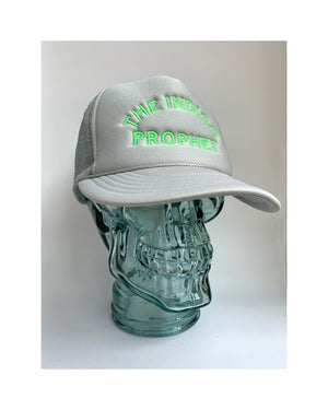 Glass mannequin skull head on white background  wearing a trucker style hat in grey with The Indigo Prophet stitched on the front in neon green.