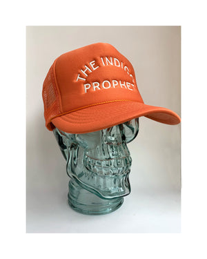 Glass mannequin skull head on white background  wearing a trucker style hat in orange aka blaze with The Indigo Prophet stitched on the front in cream.