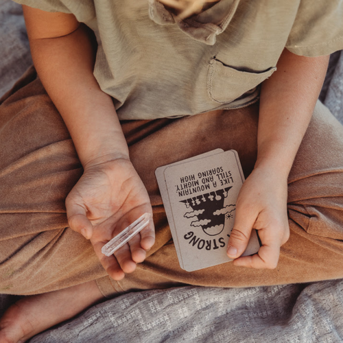 Boy sitting cross-legged holding Affirmation Cards and a crystal.
