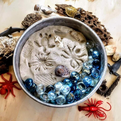 Aerial view of a bowl filled with Sand Playdough, blue pebbles and a shell.