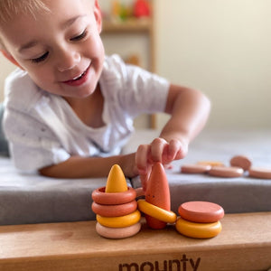 Little boy playing with wooden loose parts.