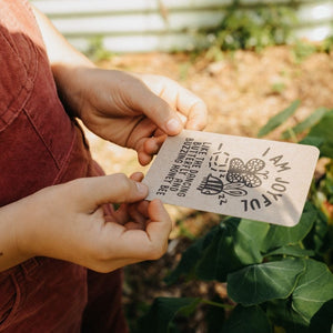 Girl in the garden holding an I am Joyful Affirmation Card.