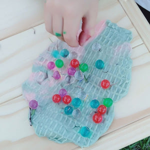 playdough and water beads with a little hand