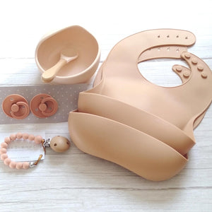 apricot silicone bib, bowl, dummies and a dummy clip