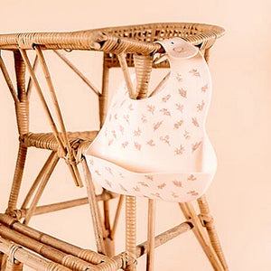 silicone-baby-bib-hanging-off-rattan-highchair