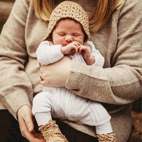 mum-holding-baby-dressed-in-knitted-bonnet-and-booties