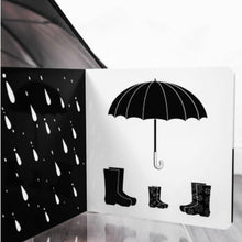 Load image into Gallery viewer, an open book showing gumboots, an umbrella and rain in black and white