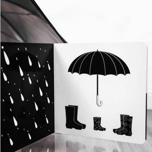 an open book showing gumboots, an umbrella and rain in black and white