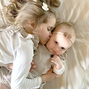 baby-girl-wearing-crochet-bow-headband-cuddled-by-sister