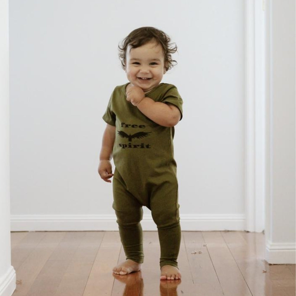 toddler boy smiling wearing an olive jumpsuit