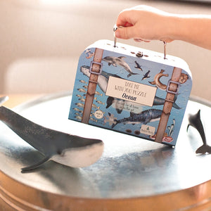 kids-suitcase-puzzle-grabbed-by-a-hand-with-a-whale-and-dolphin-figures