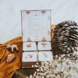 box-of-cards-open-on-a-table-with-a-pine-cone-flowers-and-wooden-deer-figures