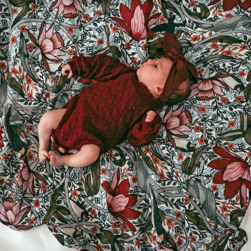 baby-girl-in-headband-lying-on-floral-wrap