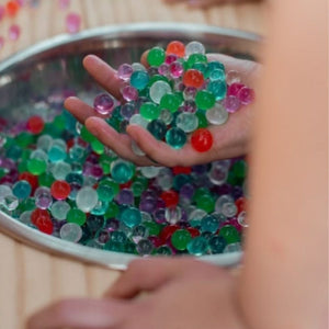 little hands grabbing a fistful of water beads