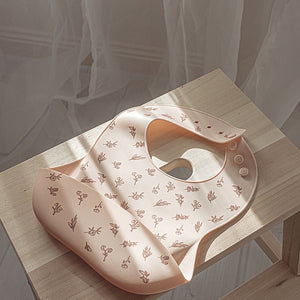 silicone-bib-lying-on-table-in-front-of-a-sheer-curtain