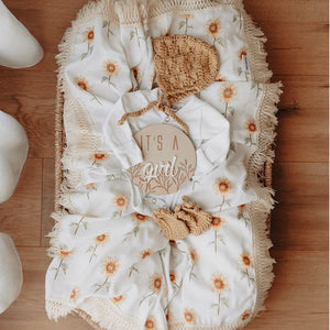 baby flat lay with milestone disc and sunflower wrap