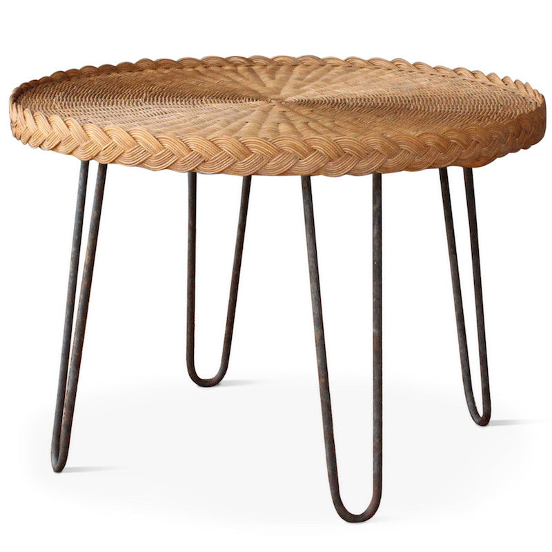 The San Remo End Table, designed by Hollywood at Home founder Peter Dunham, features a circular wicker top with Mid-century styled iron legs in a rustic patina. The table has a braided edge detail with a natural or dark wicker top.