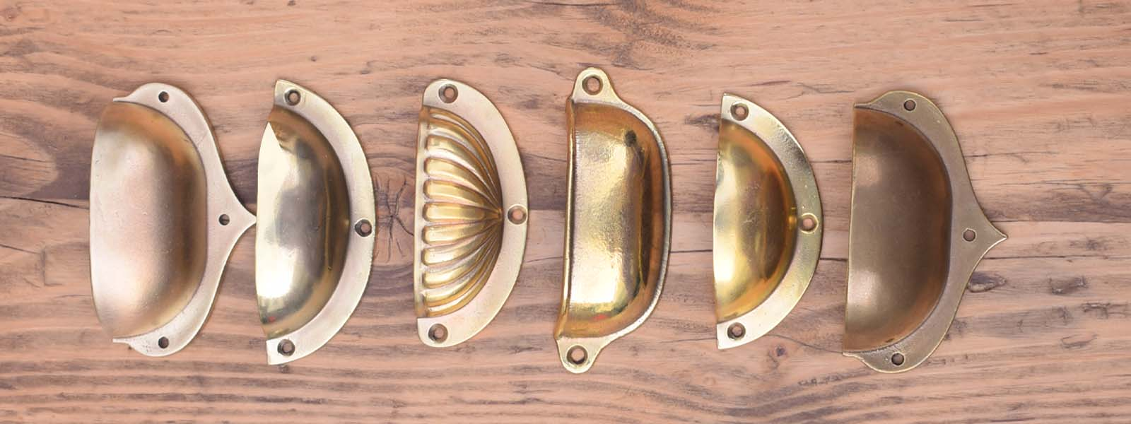 cup handles, finger pulls, brass cabinet pulls, brass drawer pulls on wood background
