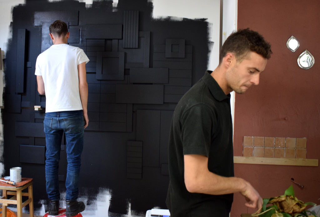 Painting the matt black handle feature wall before 100% design show