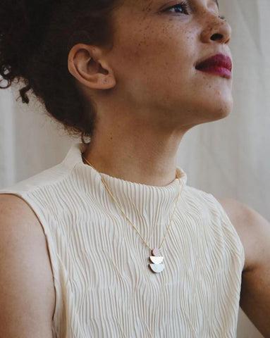 woman wearing a cream high neck top with a blush pink pendant necklace