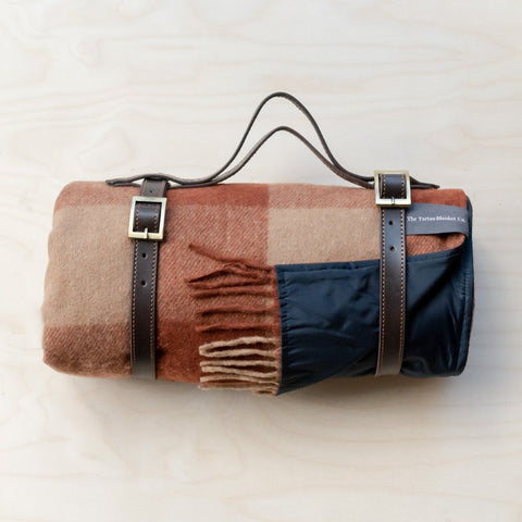rust wool tartan picnic blanket with leather straps and handle