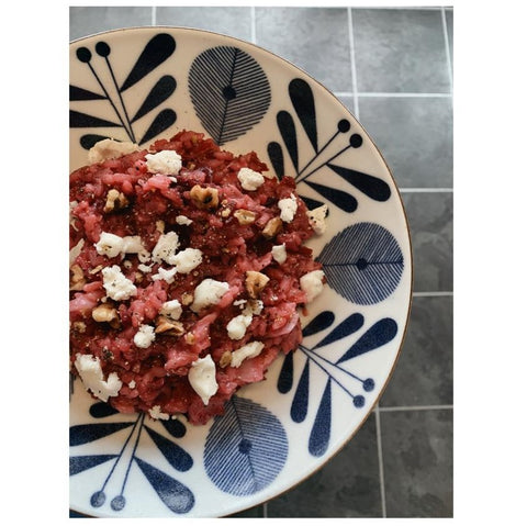 bowl of beetroot risotto with goats cheese and toasted walnuts
