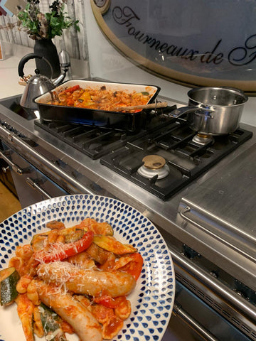 plate of baked veg and sausage pasta held infront of a lacanche range cooker