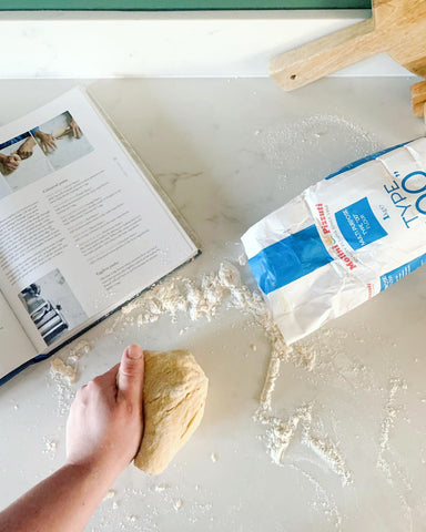 hand kneading dough with a bag of flour on the table and recipe for pasta from scratch