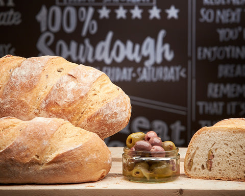 loaves of bread from casella and polegato on a table with a jar of olives in perthshire scotland