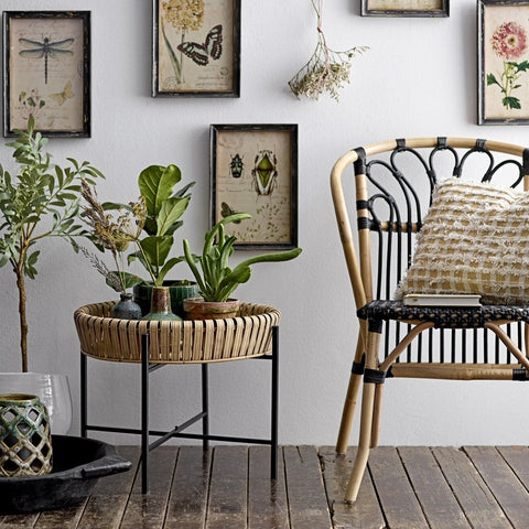 bamboo chair next to bamboo table with photo frames on the wall