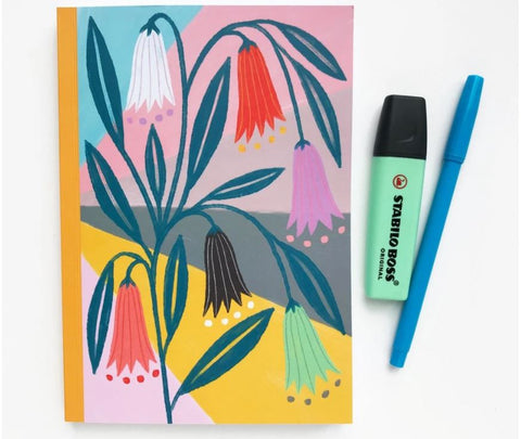 notebook with colourful floral print on cover next to a highlighter and pen