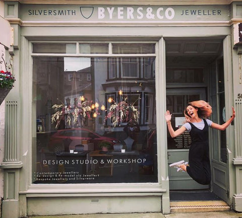 shop front of byers and co in perth city centre with woman jumping in the doorway