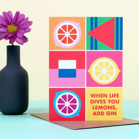 colourful greetings card next to a blue vase with a purple flower