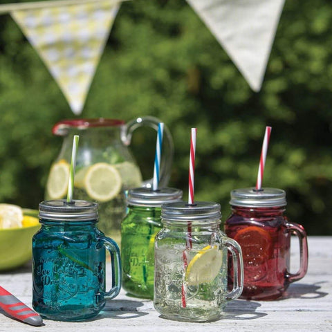 colourful glass drinking jars on a garden table with bunting in the background