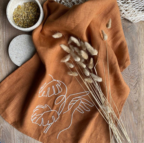rust orange linen teat towel with embroidered palm leaf and hand design from the Quince & Cook spring 2021 interior collection